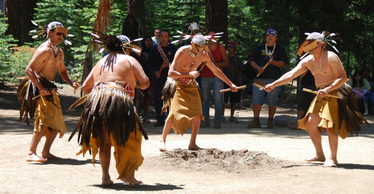 Five Native American men in traditional dance