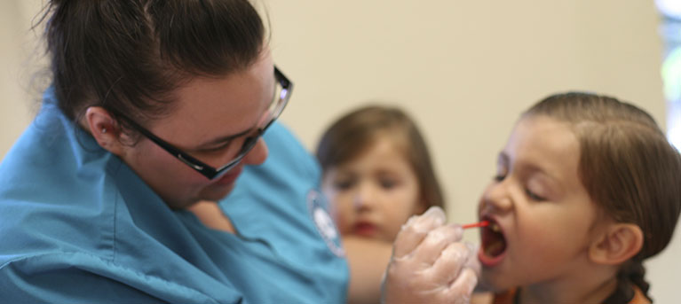An image of a female dentist in blue scrubs doing an inspection of a young girls mouth with some dental tools