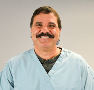 a headshot of Michael Cancilla in light blue medical scrubs